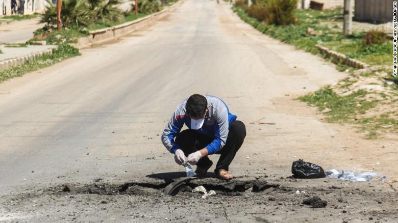 Un uomo raccoglie campioni dal cratere di impatto dell'ordigno contenente il gas sarin, Khan Shaykhun (Idlib). Credits to: Omar Haj Kadour/AFP.