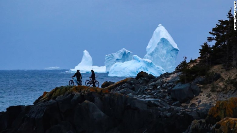 Mountain bikers stop to look at icebergs drifting off the coast of Ferryland, Newfoundland, on Tuesday.
