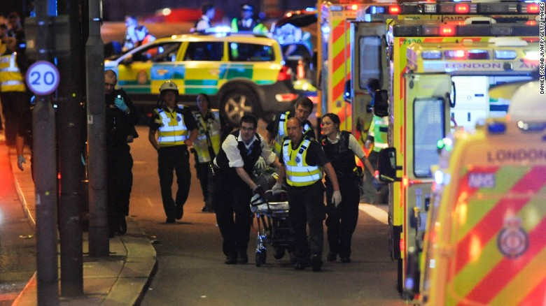 Police officers and members of the emergency services attend to a person injured in an apparent terror attack on London Bridge.