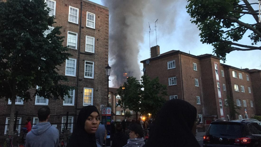 Smoke could be seen billowing over the heads of residents who gathered in nearby streets in West London to watch the blaze, which broke out in the early hours of the morning.