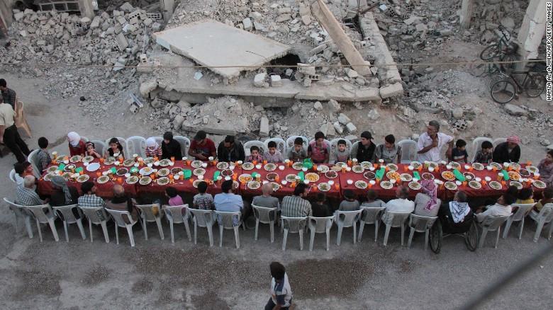 Douma residents gather in a rubble-strewn street to break fast.