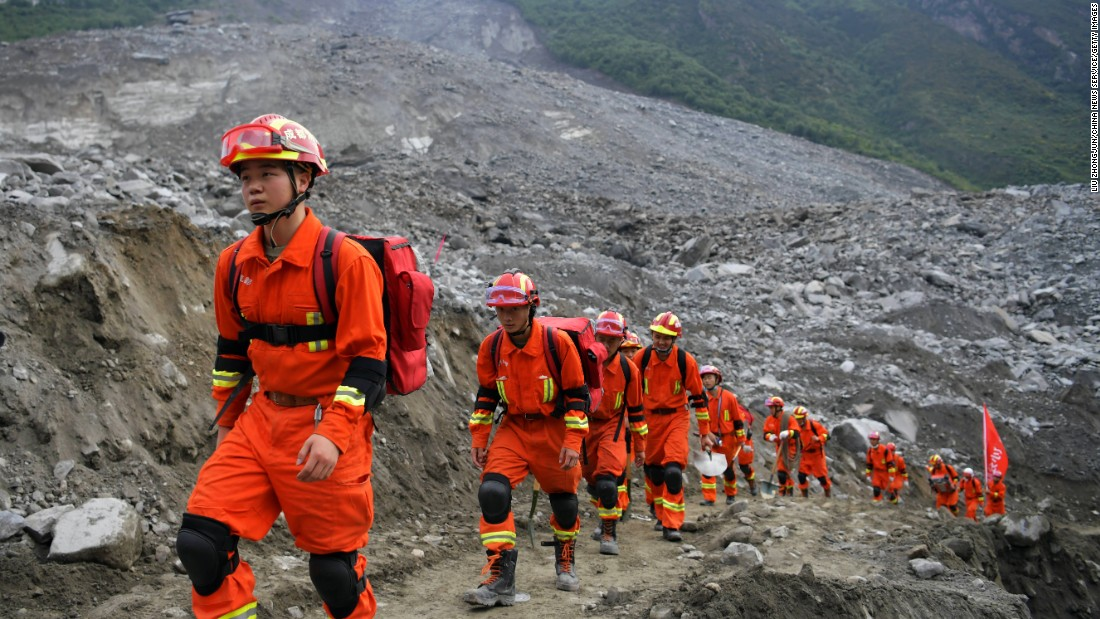 rescue workers walk to the location where they will look for survivors of a massive landslide