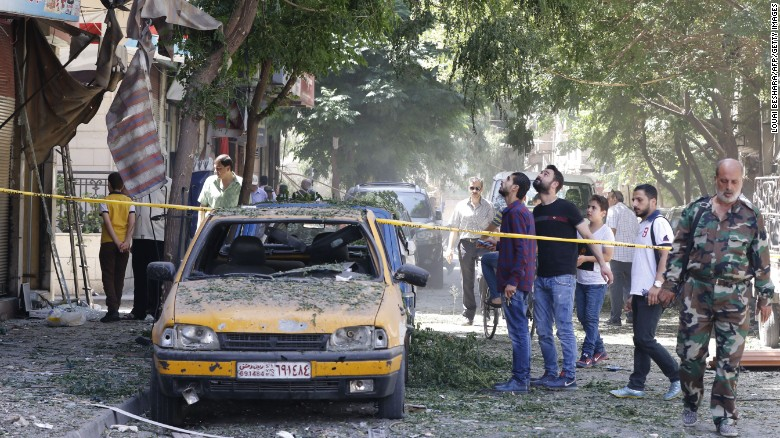 Syrian men look at a cordoned off area at the site of a suicide bomb attack in the capital Damascus' eastern Tahrir Square district.