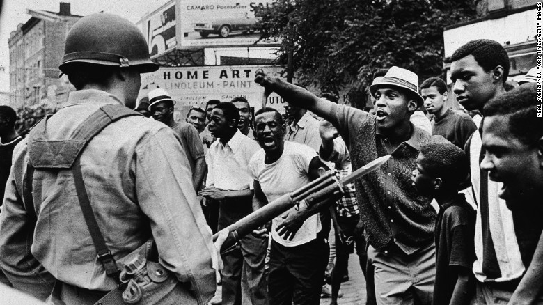 A man gestures with his thumb down to an armed National Guard man, during a protest in Newark, New Jersey, July 14, 1967.