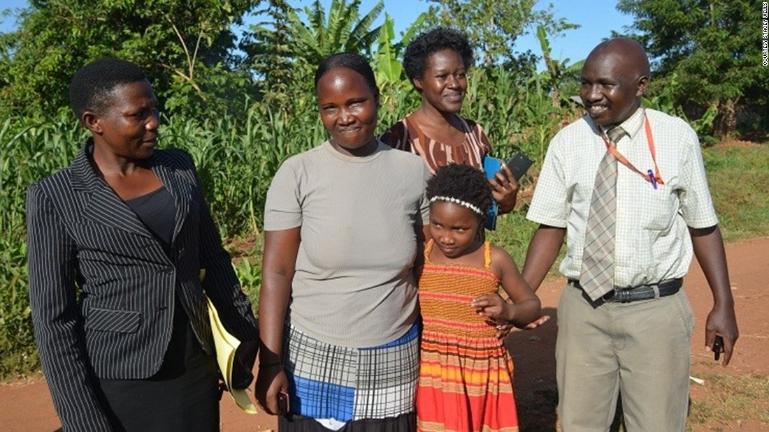 "Wells and her husband discovered the truth when they found a Facebook page for Reunite Uganda and saw a photo of a woman who claimed that her children had been taken. ""We said, 'that's Violah's mother,' "" Wells said. ""And we were just sick."" Here, Ugandan investigators join Violah and her mother (center, in gray shirt) for the reunion.<br />"