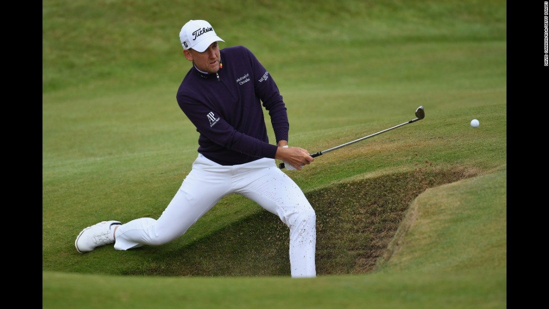 Ian Poulter of England plays out of a bunker on the seventh hole.