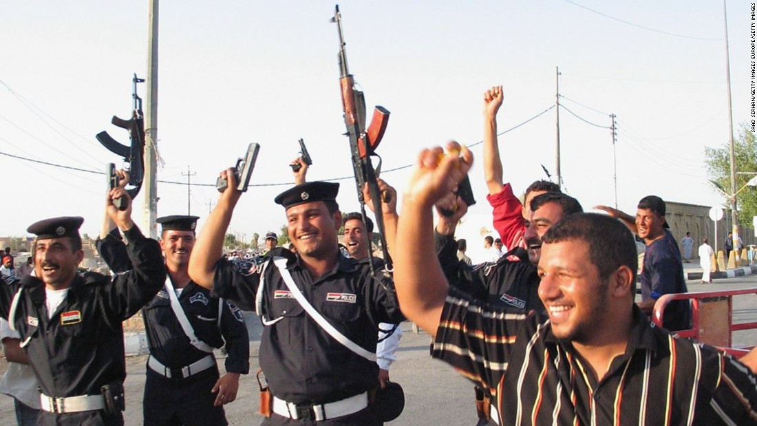 Many fired their weapons in the air in celebration, including these policemen in the Shiite city of Najaf south of Baghdad.