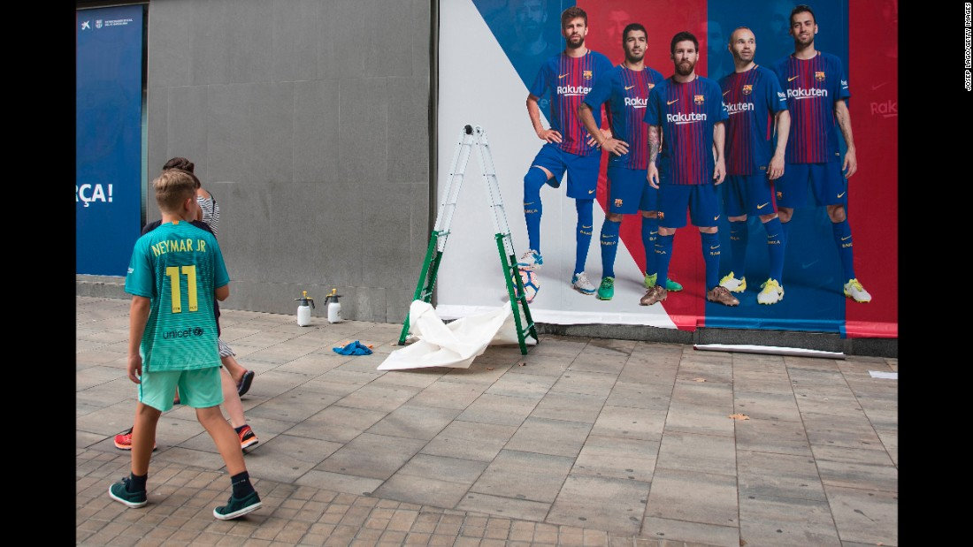 A boy wearing Neymar's jersey walks past a new Barcelona poster -- without Neymar -- as it is put up outside the Camp Nou stadium on Wednesday, August 2.