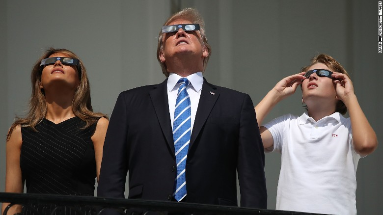 President Donald Trump, first lady Melania Trump and their son Barron Trump wear special glasses to view the solar eclipse from the Truman Balcony at the White House on August 21, 2017 in Washington, DC.
