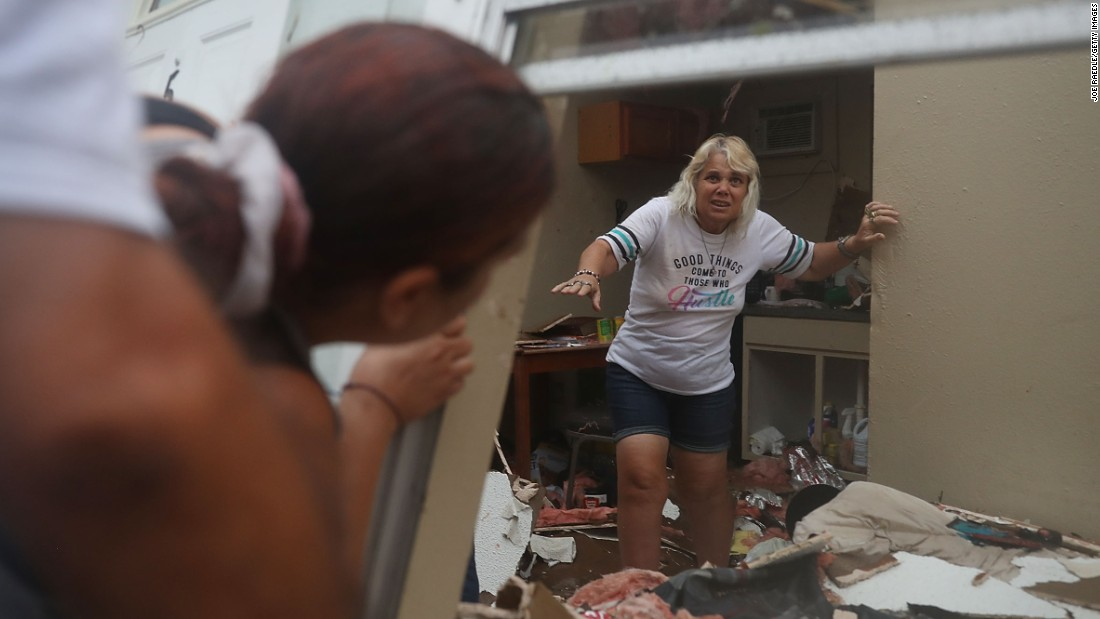 Donna Raney makes her way out of the wreckage of her home as Daisy Graham assists her in Rockport on August 26. Raney was hiding in the shower after the roof blew off and the walls of her home caved in.