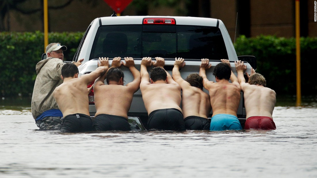 People push a stalled pickup through a flooded street in Houston on August 27.