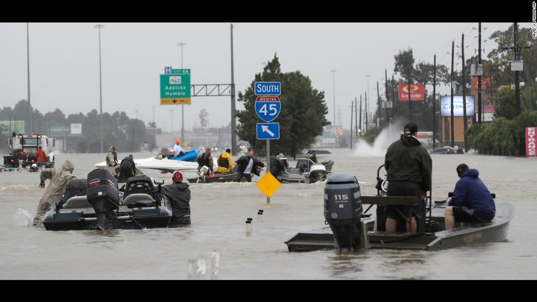 Volunteer rescue boats make their way into a flooded subdivision in Spring, Texas, on August 28.