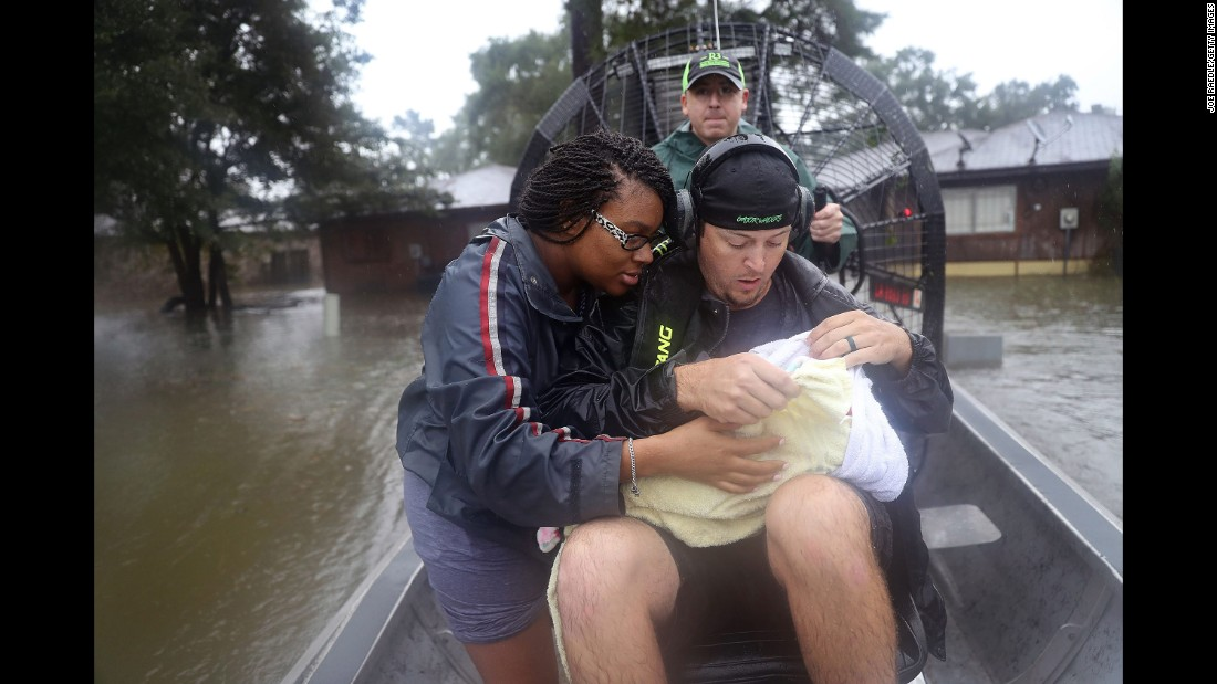 Shardea Harrison looks at her 3-week-old baby, Sarai, as Dean Mize, right, and Jason Legnon use an airboat to rescue them from their home in Houston on Monday, August 28.