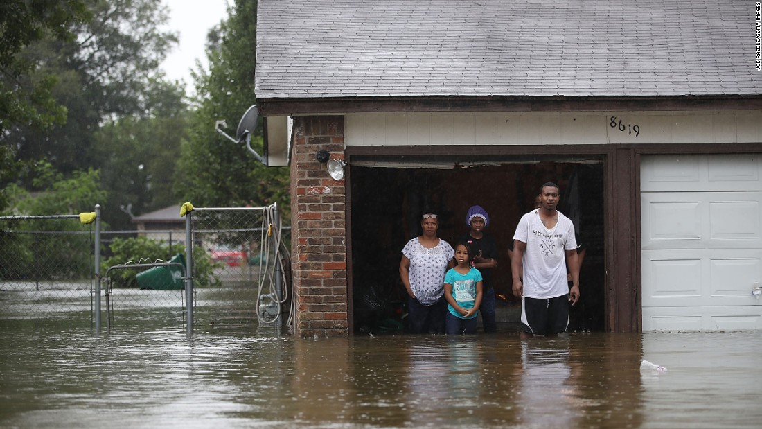People wait to be rescued from their flooded home in Houston on August 28.