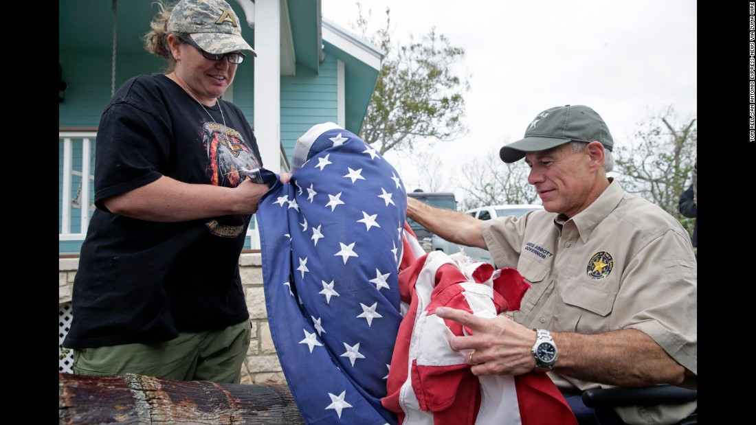 Bridget Brundrett presents an American flag to Texas Gov. Greg Abbott while he was in Rockport on August 28. The flag had been recovered from city hall after flying during the hurricane.