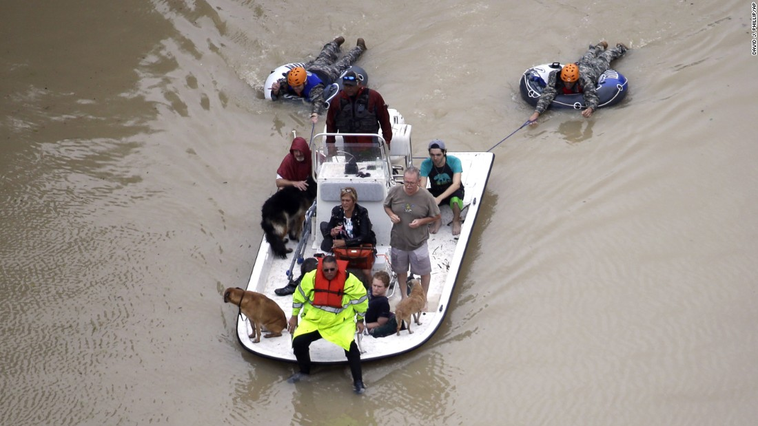 Evacuees make their way though floodwaters in Houston on August 29.