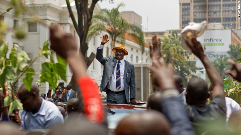 Opposition leader Raila Odinga smiles and waves to a crowd of his supporters as he leaves the Supreme Court on Friday