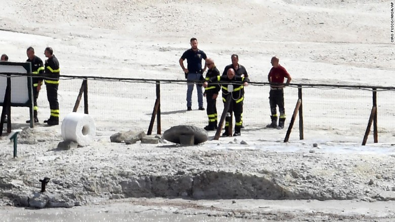 Rescue workers stand near the crater in Pozzuoli, Italy, after three people died there Tuesday September 12.