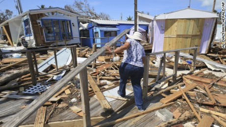 Mirta Mendez walks through the debris at the Seabreeze trailer park along the Overseas Highway in the Florida Keys on Tuesday.