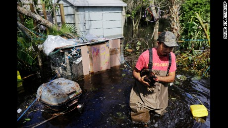 Jose Encarnacion pulls a chicken out from a cage as he retrieves belongings from his flooded home in Bonita Springs, Florida, on Tuesday.