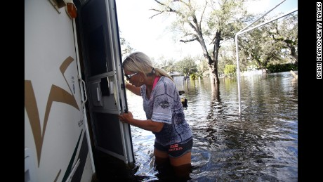 Waist-deep in floodwater, Shelly Hughes gets her first look at the inside of her flooded camper at the Peace River Campground in Arcadia, Florida, on Tuesday.