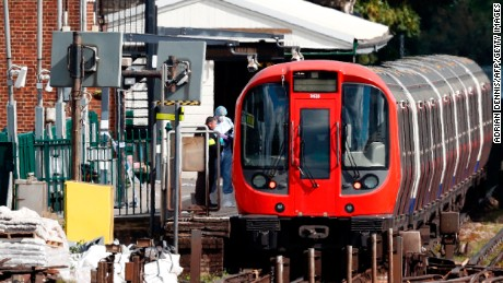 Police forensics officers work by a Tube train at Parsons Green station on Friday.