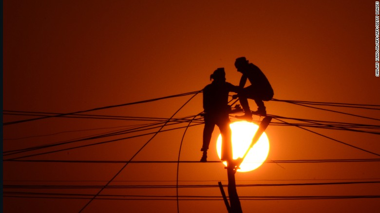Indian workers adjust electricity cables set up temporarily on the banks of the river Ganga, December 26, 2015.
