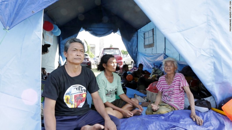 Wayan sits with his family at the Swecapura evacuation center in Bali.