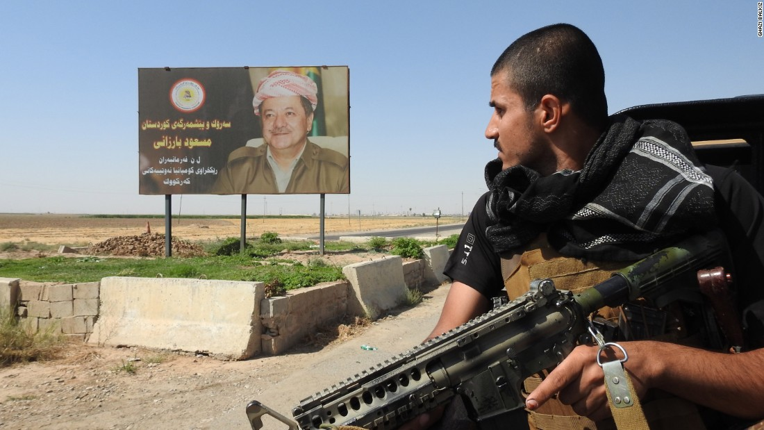 A Peshmerga fighter looks at a billboard of Kurdistan Regional President Masoud Barzani.