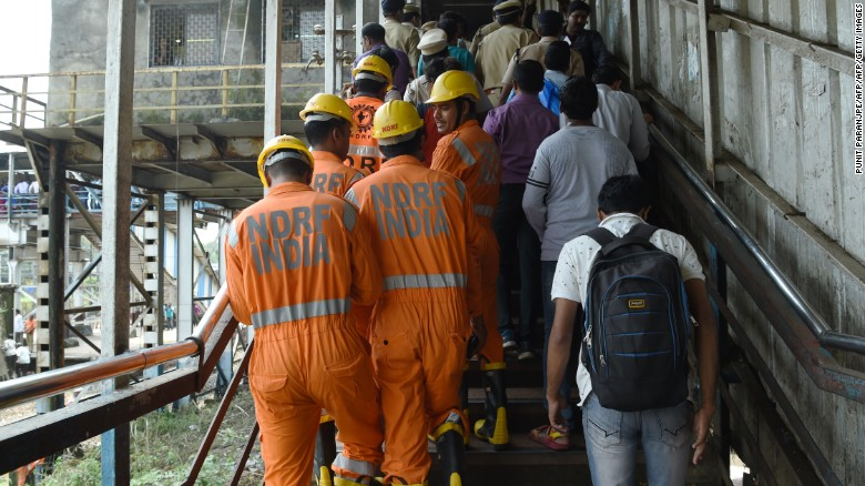 Indian rescue teams inspect the bridge where the deadly stampede in Prabhadevi train station took place.