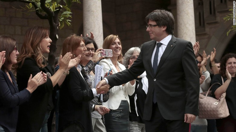 Catalan President Carles Puigdemont shakes hands with Catalan government employees Monday.