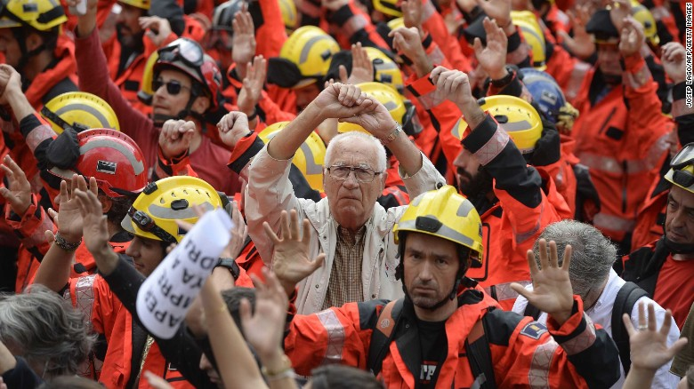 Protesters joined by firefighters raise their hands as they gather during a general strike in Barcelona Tuesday.