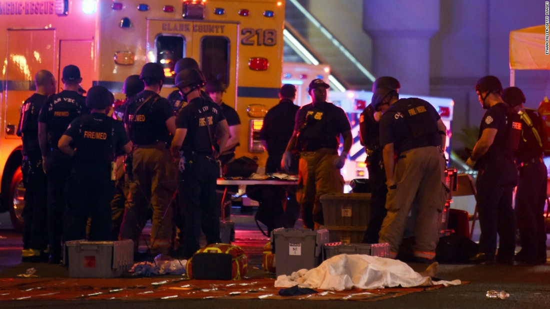 A body lies under a sheet as fire and rescue personnel respond to Sunday's shooting in Las Vegas.