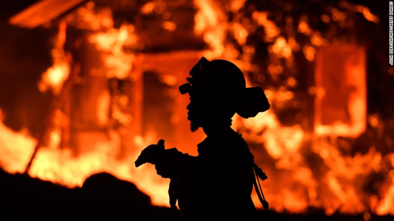 A firefighter monitors flames as a house burns in the Napa wine region of California on Monday.