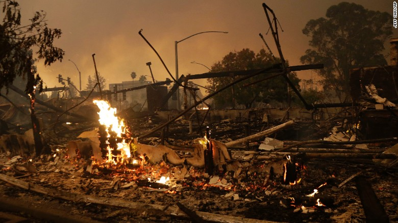 Flames rise from the remains of a burned commercial building in Santa Rosa, California on Monday.