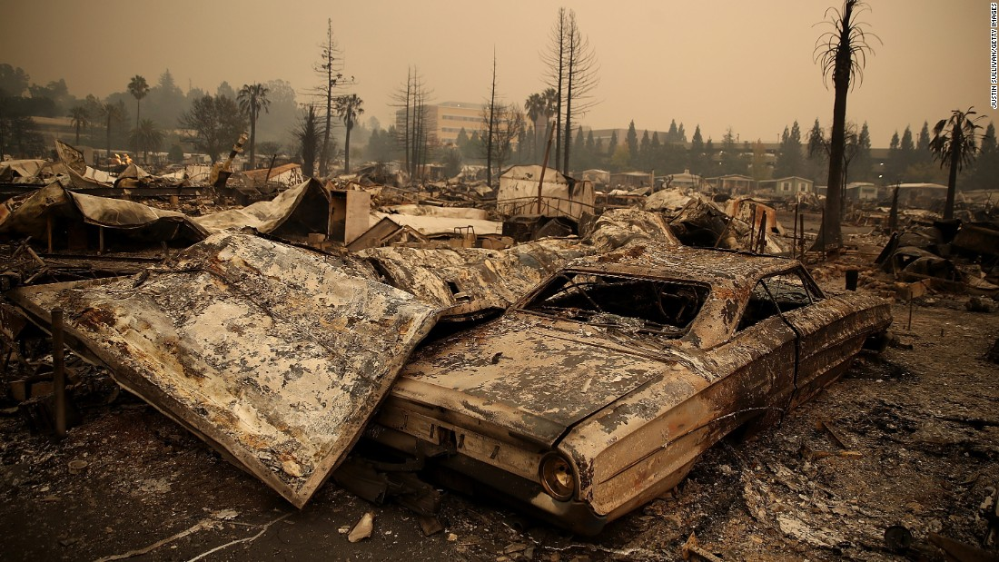 The remains of fire-damaged homes and cars smolder at a Santa Rosa trailer park on October 9.