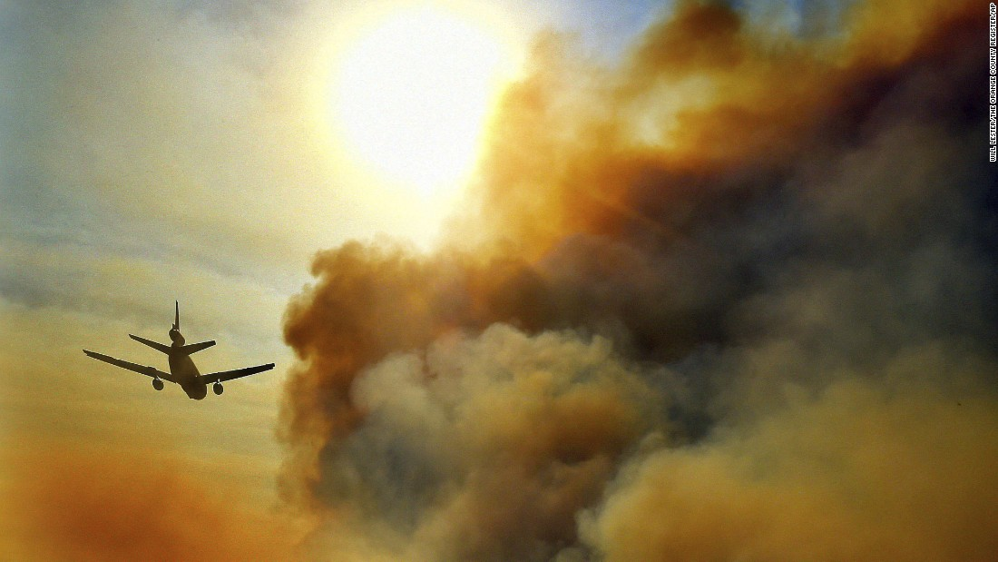 A firefighting plane helps battle a blaze just north of Tustin on October 9.
