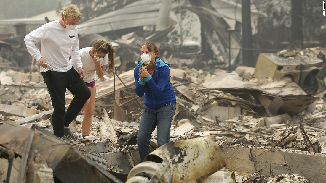Mary Caughey, center in blue, reacts after finding her wedding ring in the remains of her home in Kenwood on October 10.